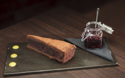 Chocolate cake served with a citrus fruit sauce and blackberries in syrup
