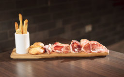 Ham and salami board with a potato, pecorino cheese and rosemary sandwich and breadsticks